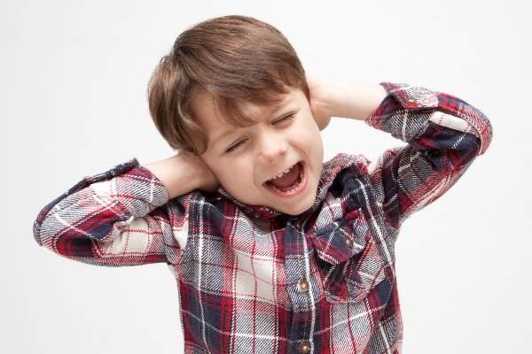 耳をふさいで苦しむ少年