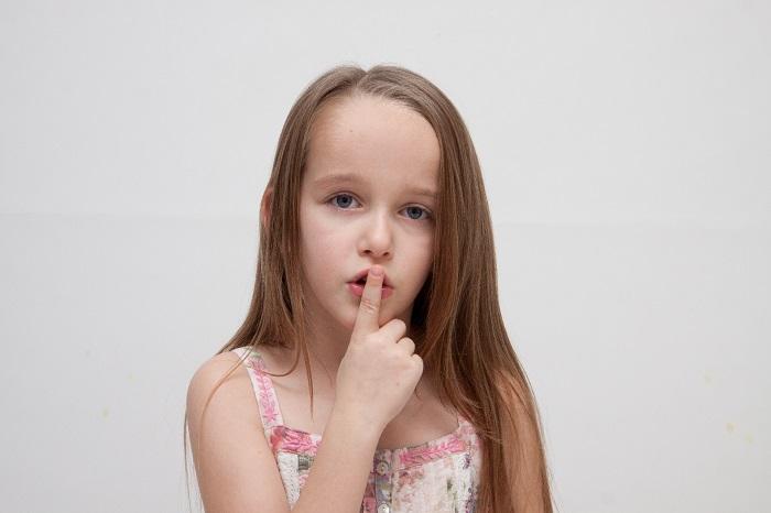 口に指を当てた少女