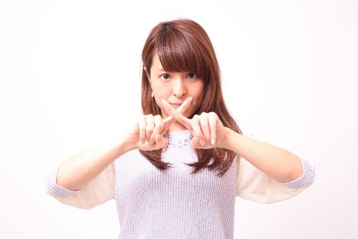 指でバツ印を作る女性