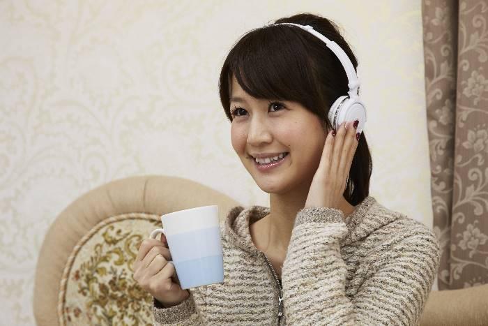 ヘッドフォンを着けてコーヒーを飲む女性