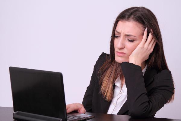 パソコンを見て顔をしかめる女性
