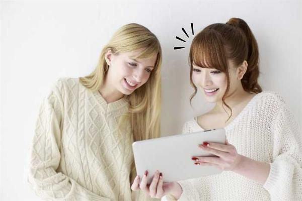 タブレットを見ながら会話を楽しむ外国人と日本人の女性