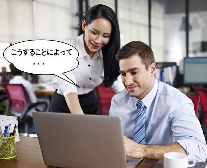 ノートパソコンを使うアジア人女性と白人男性