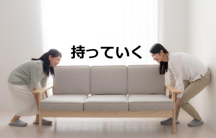 ソファーを運ぶ女性