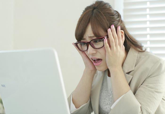 パソコンを見て困った顔をする女性