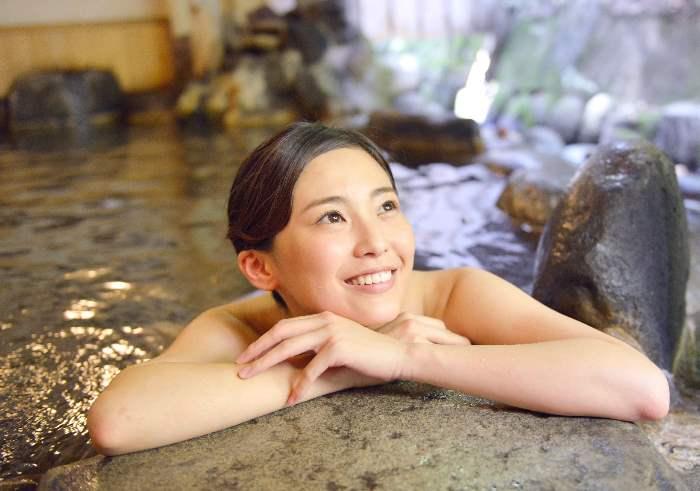 幸せな顔で温泉に入る女性