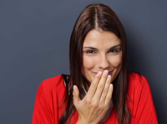 口に手を当てて笑う白人女性
