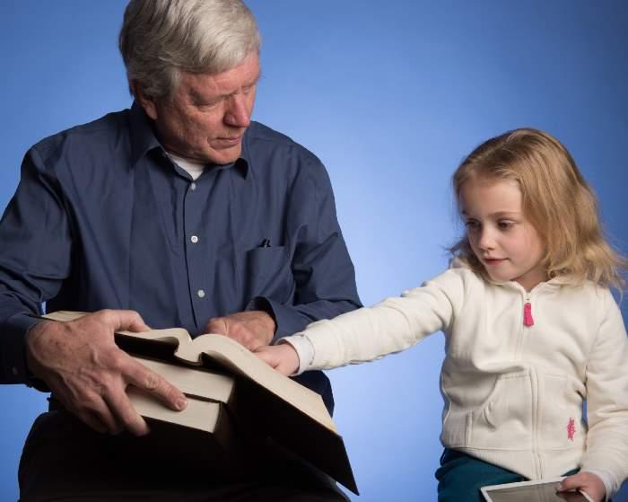 本を指さす少女と老人
