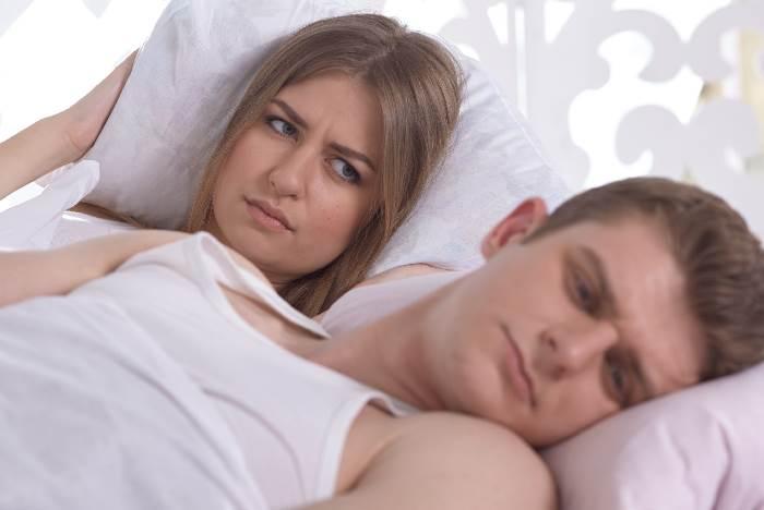 ベッドで眠る外国人の男女