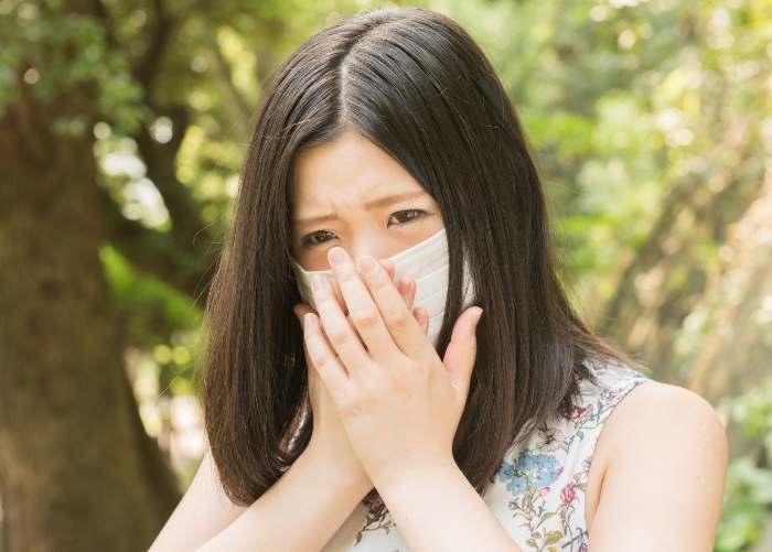 マスクをして口を押さえる女性