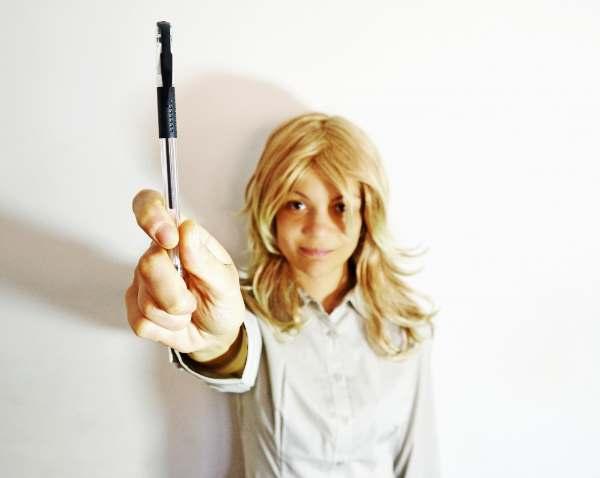 ペンを差し出す金髪の女性