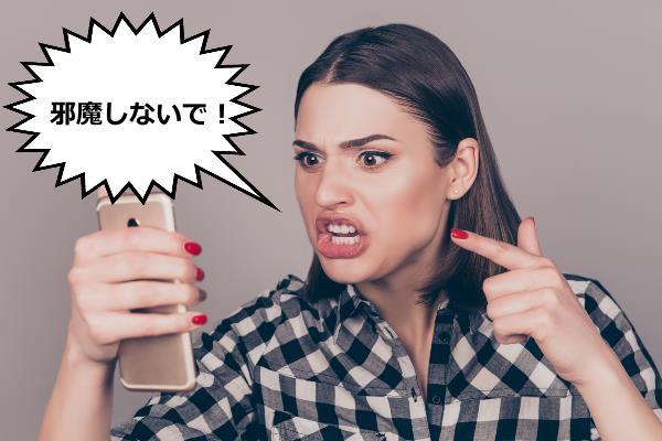 スマートフォンに向かって怒っている女性