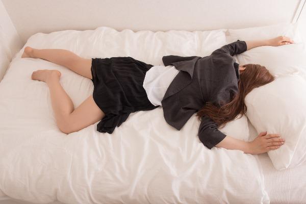 ベッドで倒れたように眠る女性
