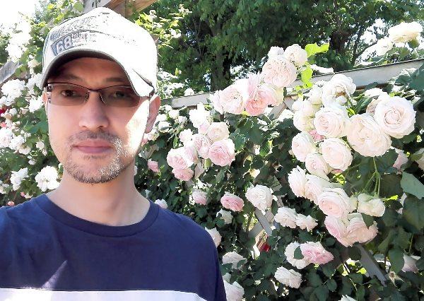 バラを背景にした男