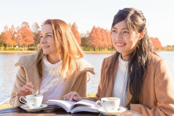 水辺でお茶を飲む女性二人