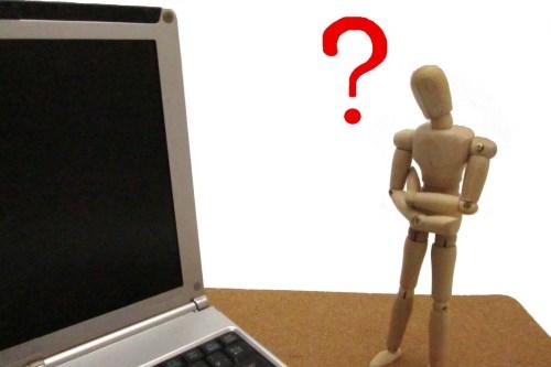 パソコンの前で考える人形