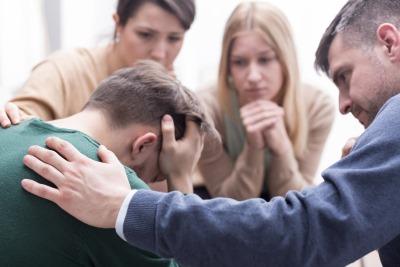 泣く男性と励ます人たち