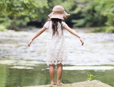 川のそばに立つ少女