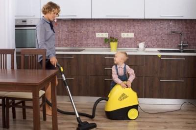 キッチンで掃除機をかける母と子供
