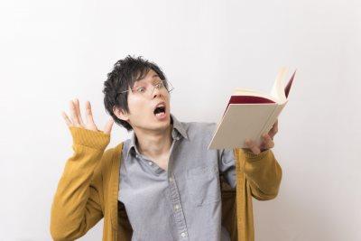 本を見て驚く男性