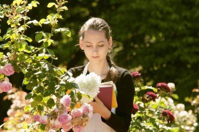 花に囲まれて本を読む女性