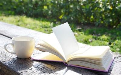 庭のテーブルにカップと本がある