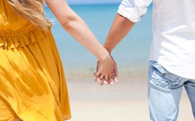 ビーチで手をつなぐカップル