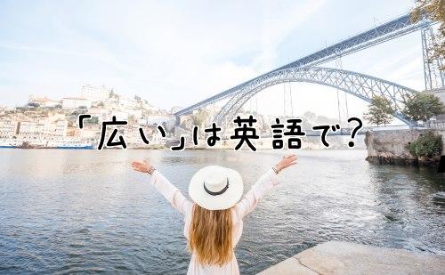 川の前で両手を広げる女性
