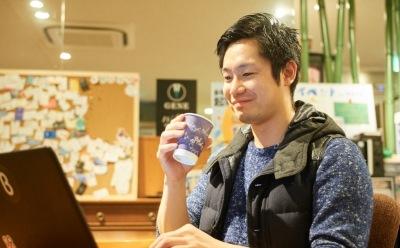 コーヒーを飲みながら微笑む男性