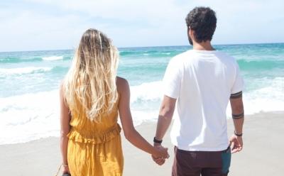 海岸を歩く外国人のカップル