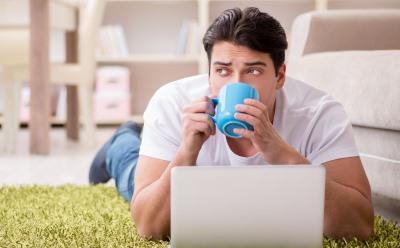 腹ばいでコーヒーを飲む男性