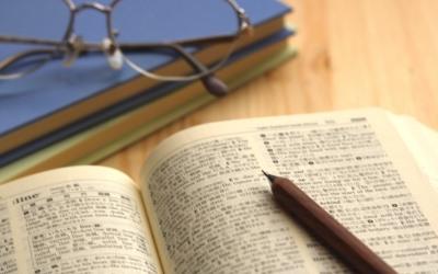 英語の辞書とメガネとペン