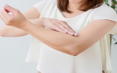 肘を抑える女性