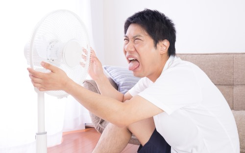 湿度が高い部屋で扇風機にあたる男