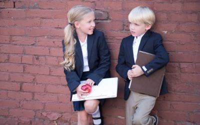 壁にもたれて立つ少女と少年