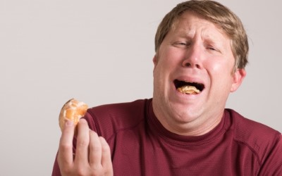 パンを食べてまずそうな顔をする男