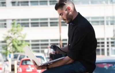 背中を丸めてパソコンを使う男