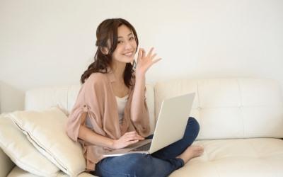 ベッドでパソコンを使う女性