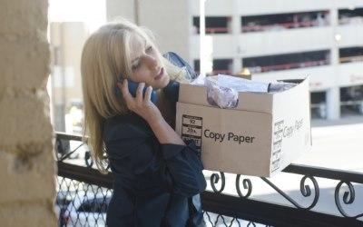 箱を運びながら電話する女性
