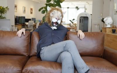 ソファーに座るライオン顔の男