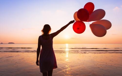 海岸で風船を持つ女性
