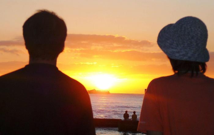 海岸で夕日を見るカップル