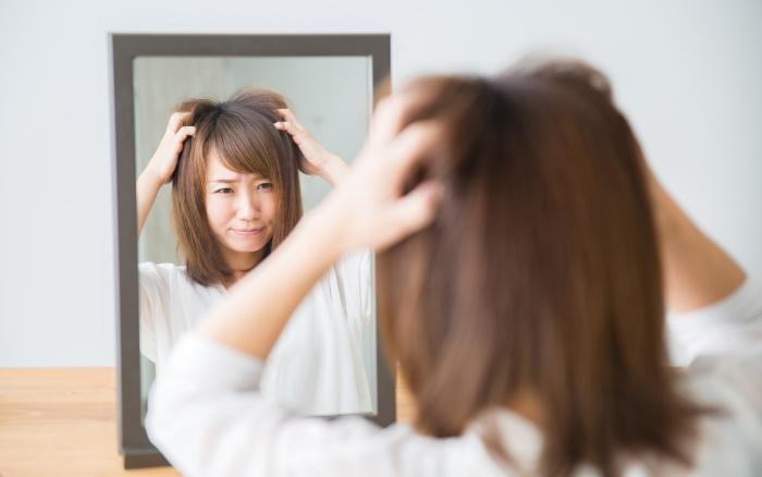 鏡を見てイライラする女性