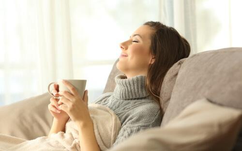 コーヒーを飲みながらリラックスする女性