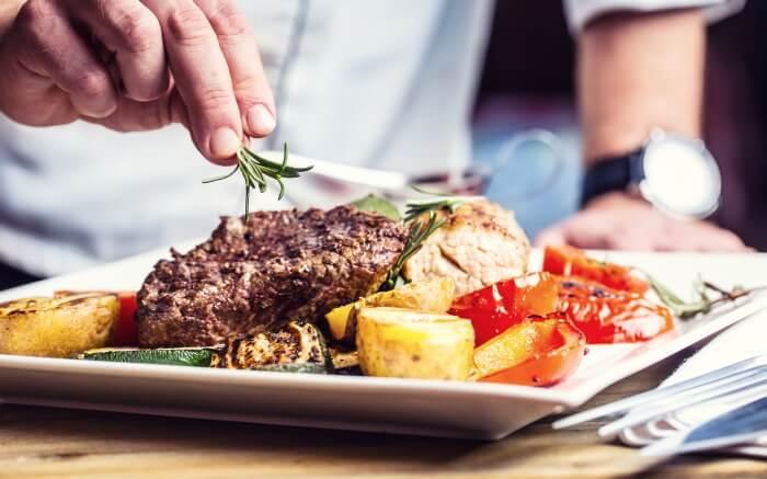 ステーキを盛り付けるシェフ