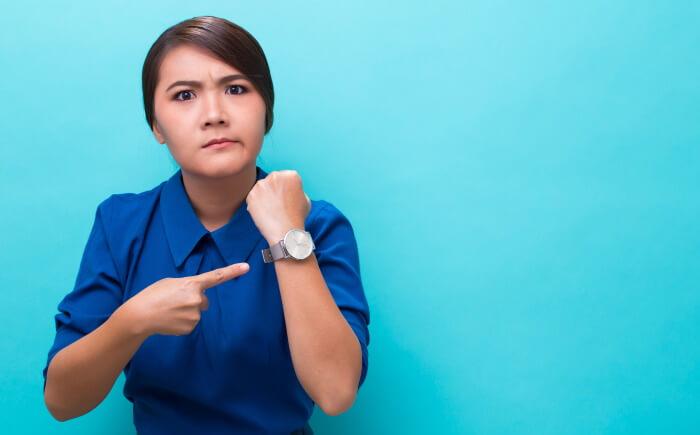 時計を指さすせっかちな女性