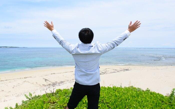 海岸でバンザイする男性